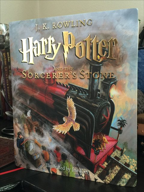 Book cover showing the Hogwarts Express steaming along the track with Hedwig flying to its side above Harry who stands with other students amongst the luggage